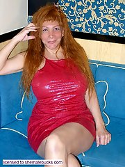 Mature shemale in a red dress strips for you